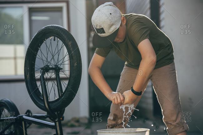 Boy cleaning bmx bike on yard
