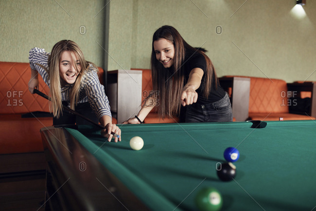 Two happy friends playing billiards together