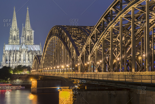 June 14, 2018: Germany- Cologne- view to lighted Cologne Cathedral with Hohenzollern Bridge in the foreground