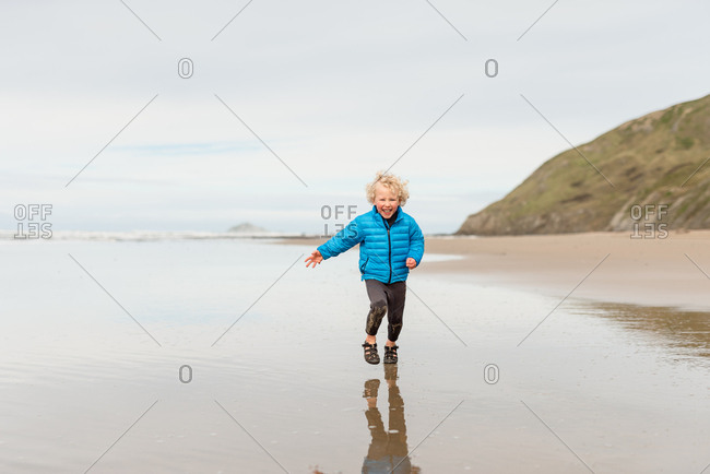 Front view of happy blonde curly haired boy running at a beach