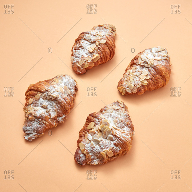 Set of delicious croissants with powdered sugar and almond flakes on a beige background with space for text. Sweet snack. Flat lay
