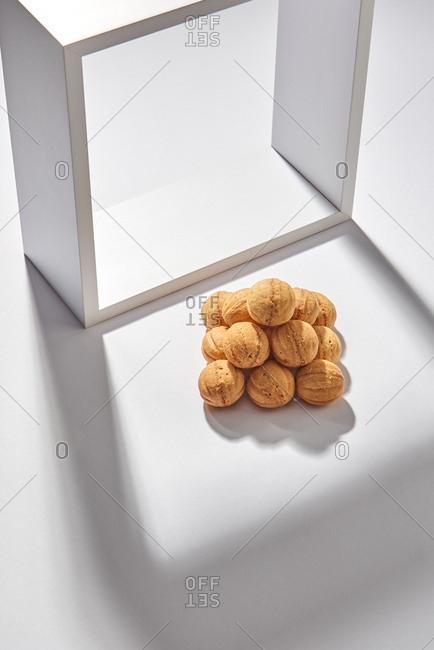 A pile of freshly baked biscuit in the shape of a nut presented on a light background with shadows from a wooden frame and copy space. Flat lay