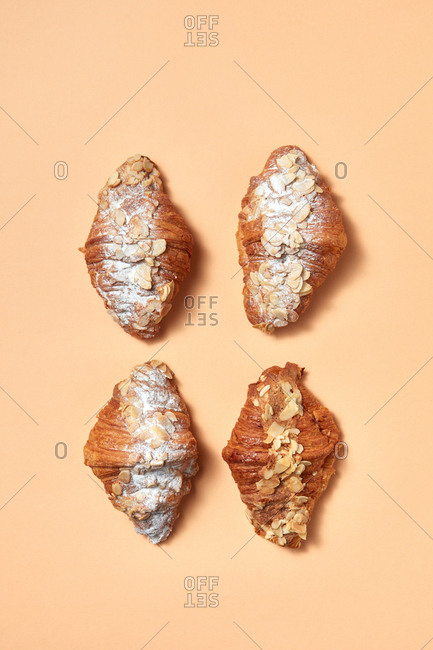 Fresh croissants with almond flakes and powdered sugar presented on a beige background with copy space. Sweet snack. Flat lay