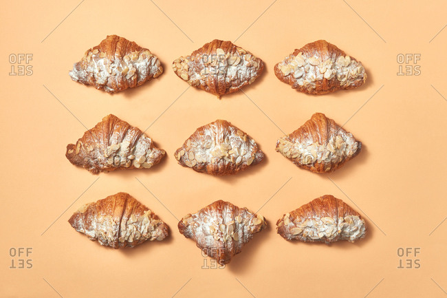 Pattern of freshly baked homemade croissants with almonds and powdered sugar on a beige background with space for text. Flat lay