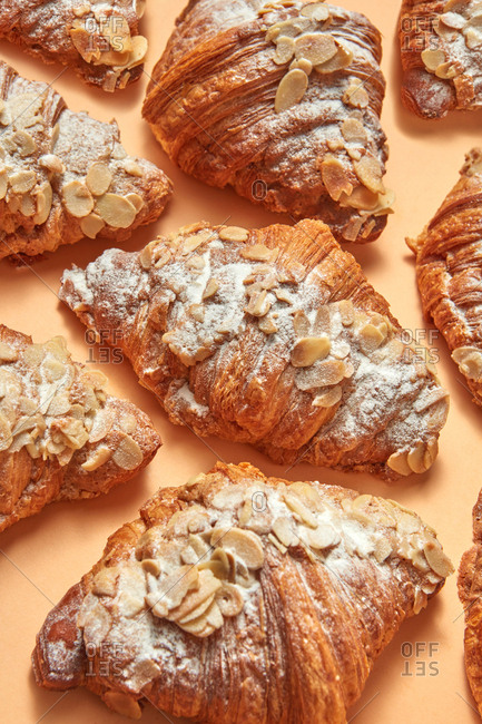 Closeup of homemade croissants with almonds and icing sugar on a beige background. Sweet snack. Flat lay