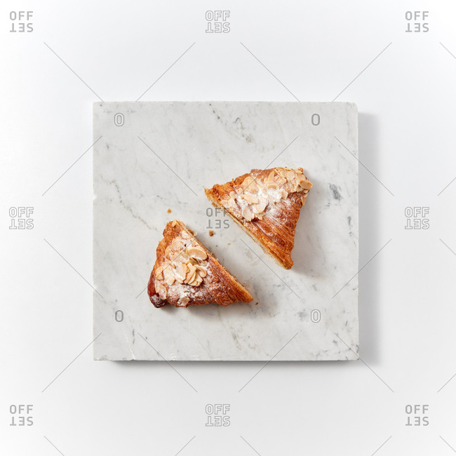 Cut croissant with icing sugar and almond flakes presented on a marble board around a light background with space for text. Flat lay
