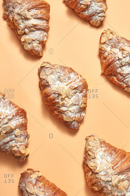 Collection of sweet croissants with almond flakes and icing sugar presented on a beige background. Flat lay