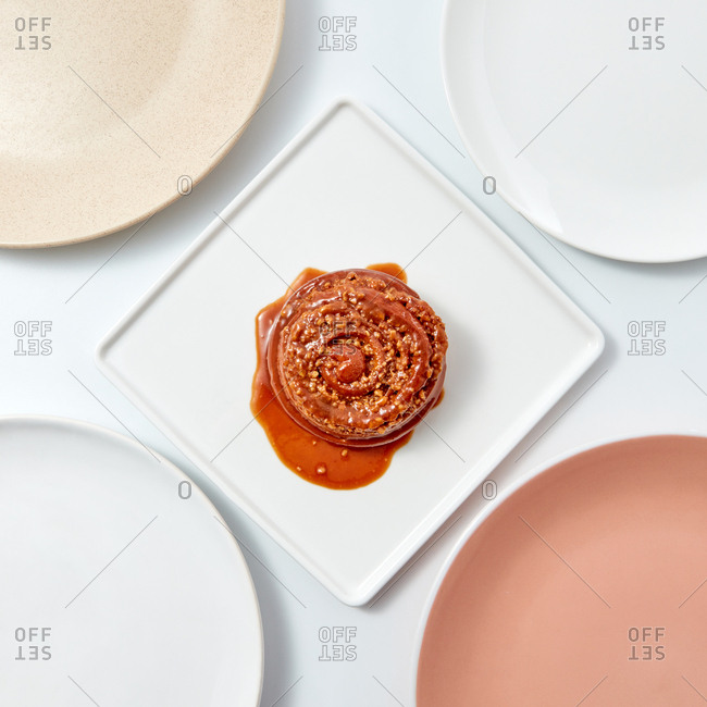 Cinnamon bun with caramel sauce and nuts in a square plate on a light background with copy space. Flat lay