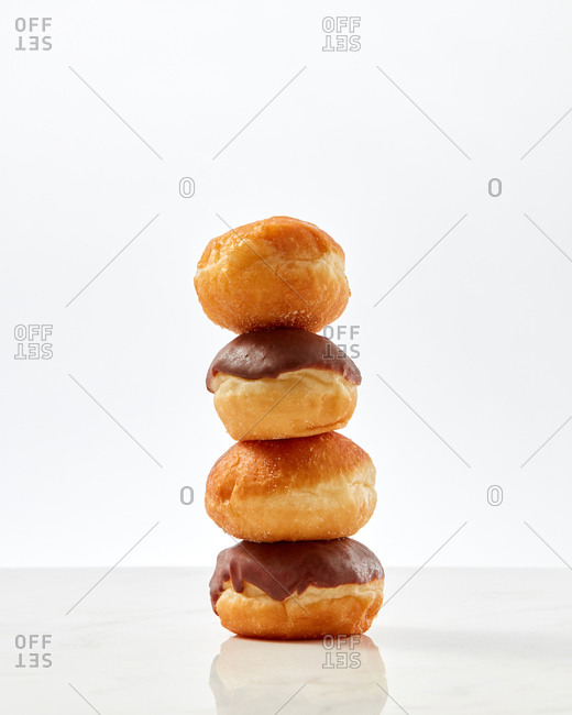 Donuts with chocolate icing presented as a stick on a light background with copy space for text.