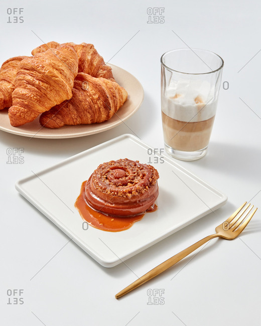 Cinnamon sweet bun with caramel and nuts, croissants and coffee drink in a glass around a white background. Sweet snack
