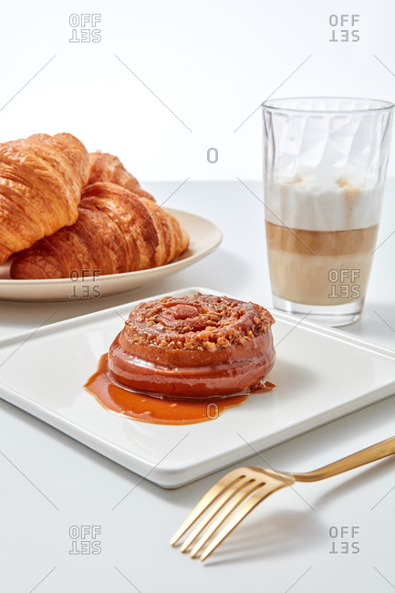 Fresh croissants bun cinnamon rolls with nuts and caramel, coffee drink in a glass on a white table. Sweet dessert