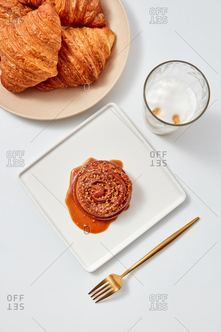 Croissants, bun with caramel sauce and nuts in a plate with a fork and a glass of coffee drink around a white background. Flat lay