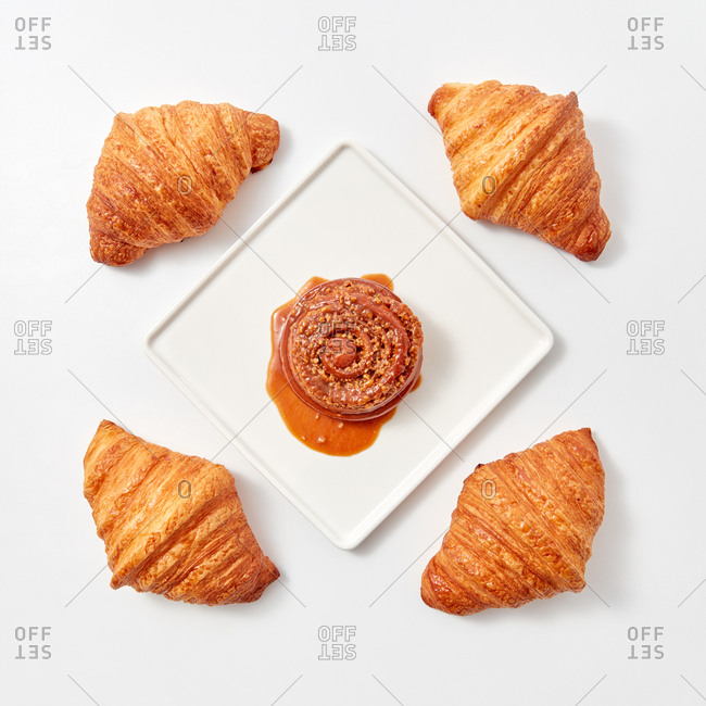 Bun with nuts and caramel in a plate around croissants on a white table. Flat lay