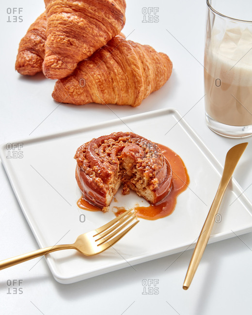 A cut bun with caramel and nuts in a plate with a fork, spoon beside croissants and a glass of coffee drink on a white table