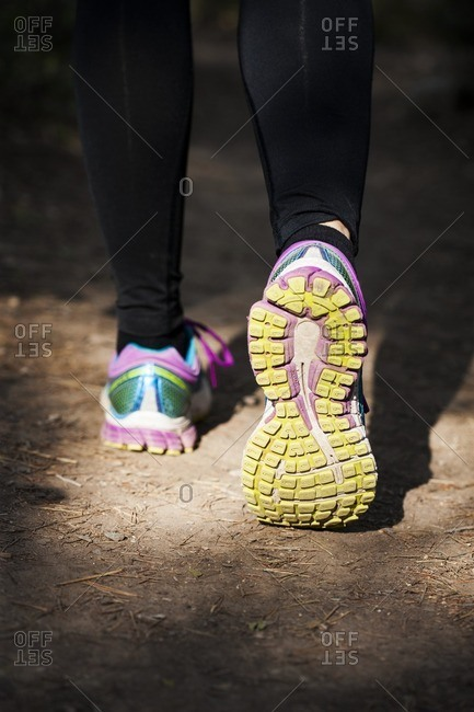 Person walking on a path. Close-up of walking shoes on a sandy path.