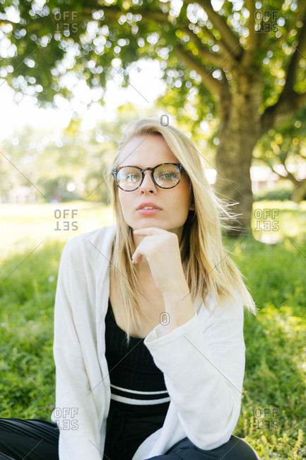 Thoughtful young blonde woman looking at the camera