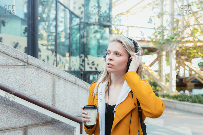 Young woman listening to music in urban ambience