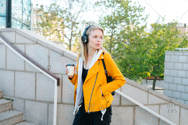 Young woman with headphones on grabbing tea in the city