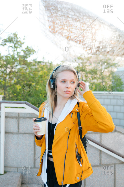 Young woman with headphones on grabbing tea in European city