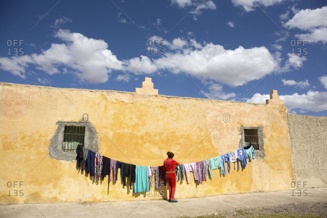 Meknes, Morocco - April 8, 2019: Woman hanging clothing to dry on a line between two windows on a yellow wall