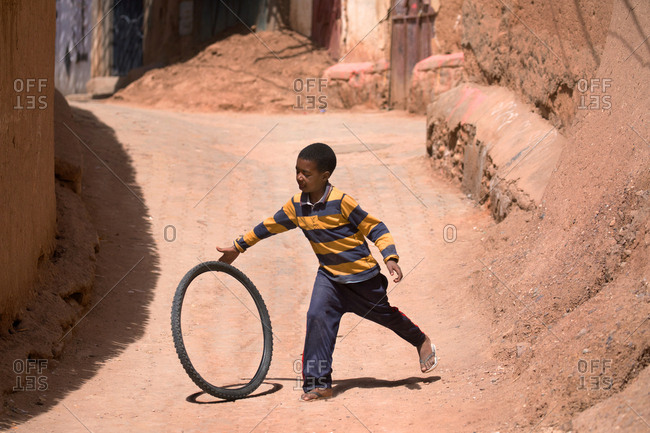 Ait Benhaddou, Morocco - April 12, 2019: Unidentified young boy plays with old tire along a dirt road in the city