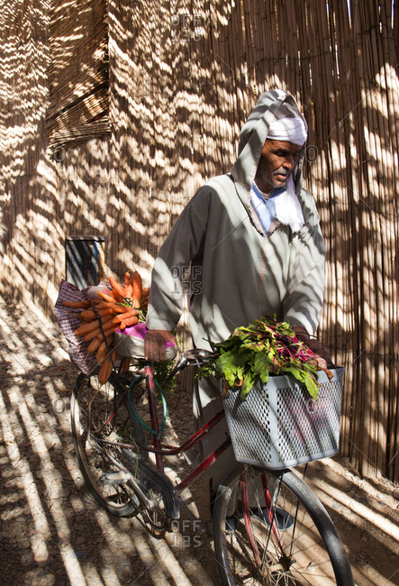 Rissani, Morocco - April 9, 2019: Man transporting vegetables and food past a bamboo thatched wall in dappled afternoon light