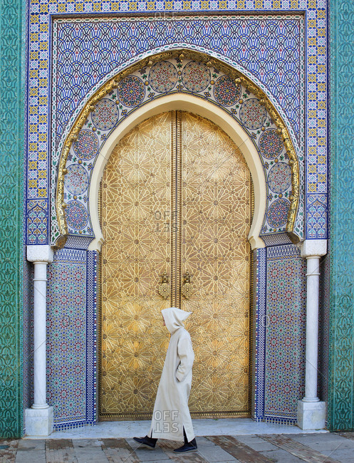 Moroccan man walking by the golden doors of the Royal Palace,