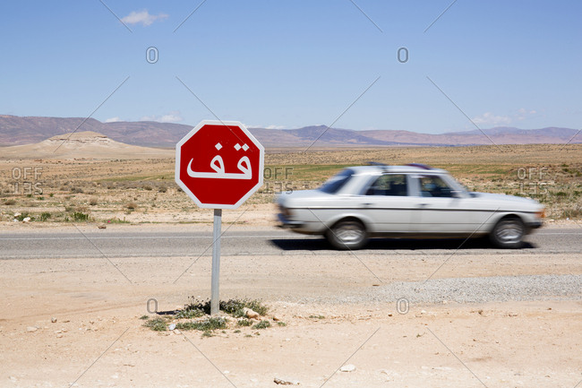 Car speeding past a stop sign on the road with a backdrop of mountains outside of Morocco