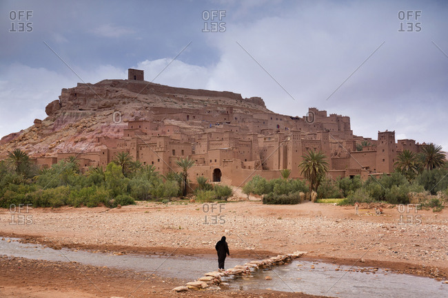 Ait Ben Haddou, Morocco - April 12, 2019: Muslim woman crossing a stream outside of a large group of stores, shops and casbahs