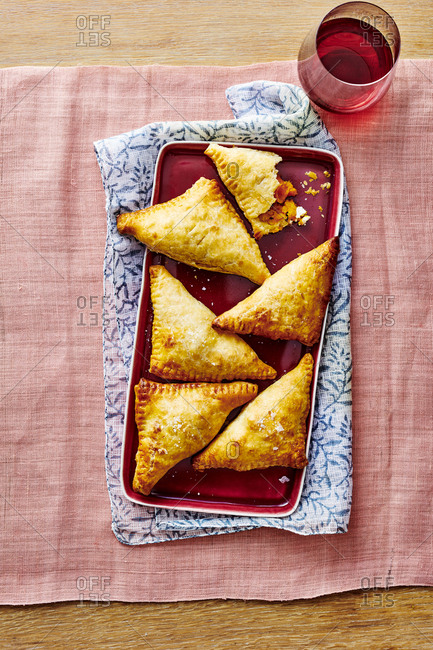 Spiced Butternut Squash Hand Pies on a rectangle plate with a glass of wine.