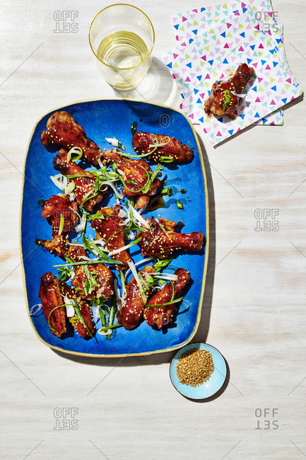 Miso Glazed Chicken Wings on Blue Plate set with a glass of water.