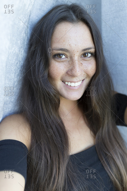 portrait of  beautiful woman with freckles against blue fabric texture