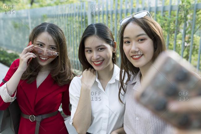 asian friends taking selfie on the street