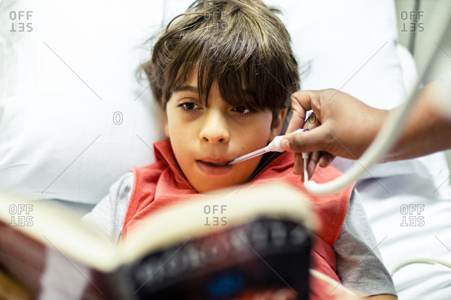 Boy lying on bed and reading while nurse is taking the temperature