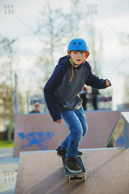 Front view of young boy skateboarding on ramp wearing blue helmet