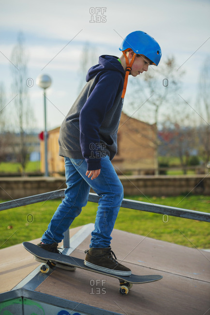 Side view of young boy with blue helmet skateboarding on skate ramp