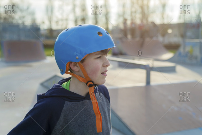 Side view of young boy skater wearing blue helmet standing  outdoors