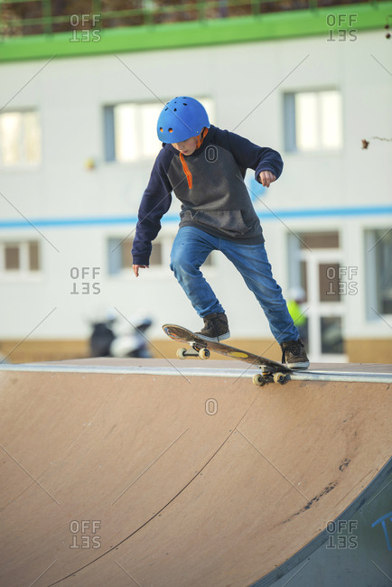 Young skater with blue helmet ready on skate ramp to perform a trick