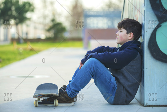 Side view of young boy leaning on skate ramp while looking away