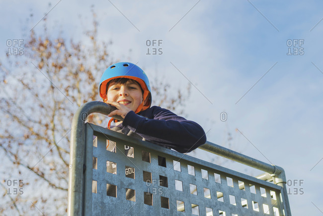 Portrait of a young boy with blue helmet, looking camera in sunny day