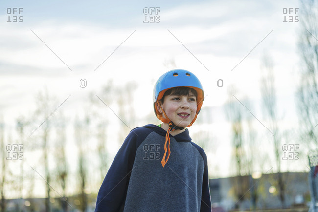 Front view of young boy skater with blue helmet while looking away
