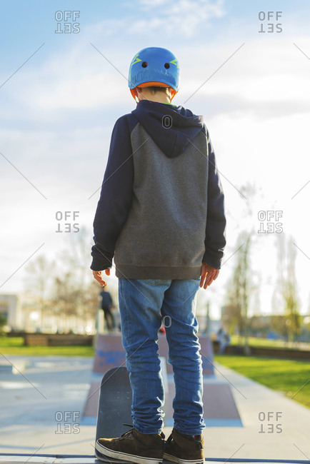 Rear view of young boy standing at skate ramp ready to perform a trick
