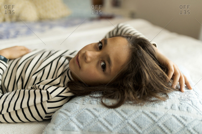 Cute young boy with messy hair lying on bed