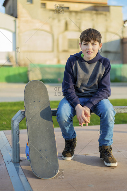 Front view of young boy sitting on flat rail looking camera, sunny day