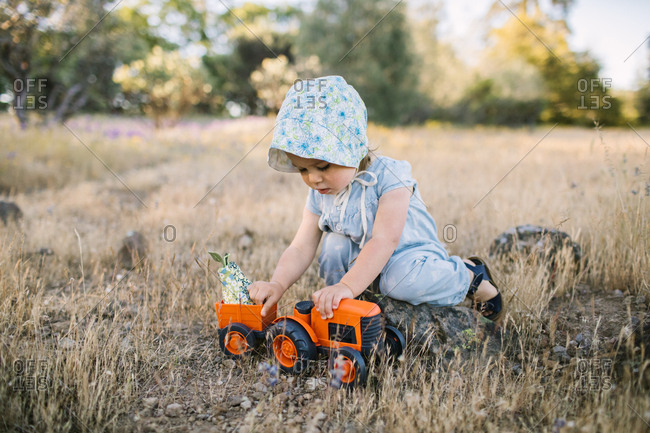 Toddler girl playing with a toy tractor in a field