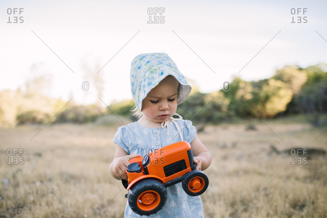 Toddler girl holds an orange tractor in a field