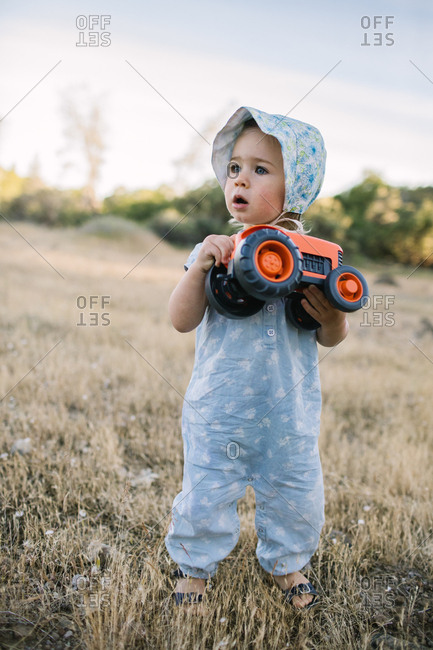 Toddler girl holds an orange tractor in a field, looking on