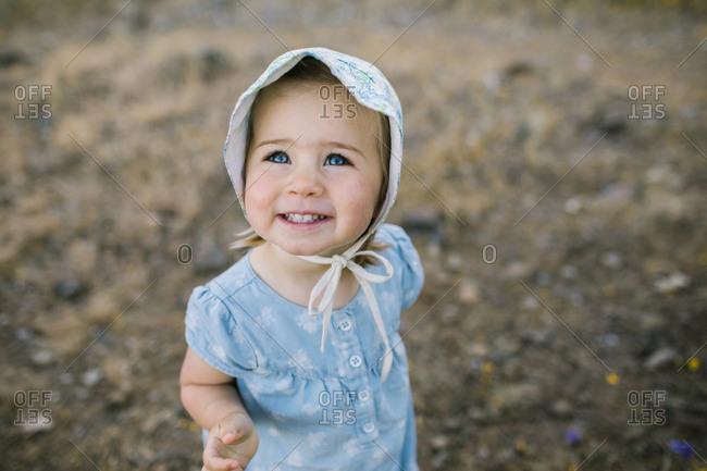 Toddler girl wearing a bonnet smiling upwards