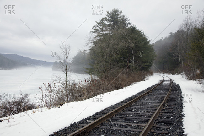 A railway track, train tracks in the snow, by a lake in the Vermont landscape, mist rising from the water, mountains in the distance.