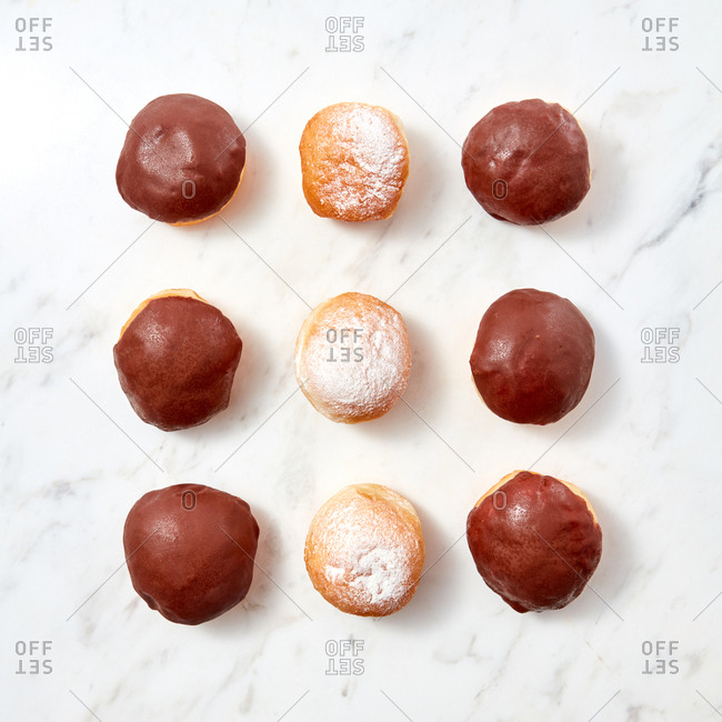 Donuts with icing sugar and chocolate icing on a marble background. Food pattern. Flat lay